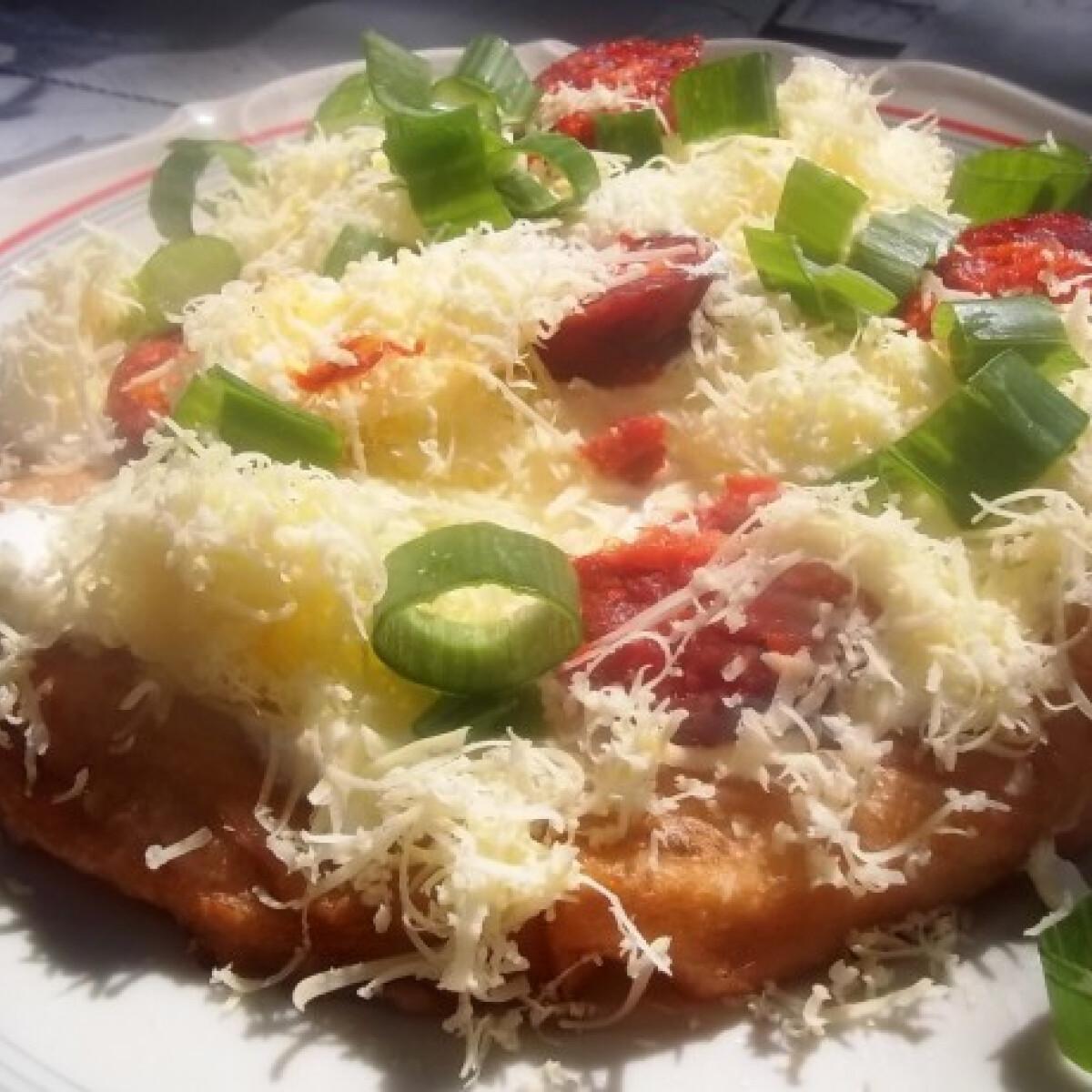 Ezen a képen: Tejfölös-kolbászos-sajtos lángos újhagyma zöldjével